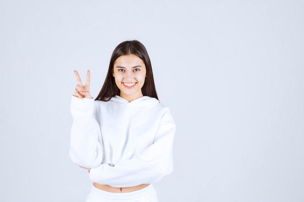 Положительная модель молодой девушки показывает знак победы.