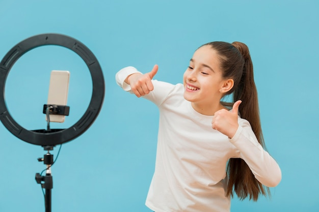 Positive young girl recording video for blog