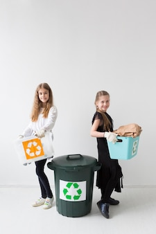 Positive young girl recycling together