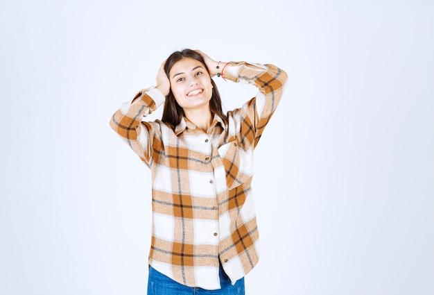 Позитивная молодая девушка стоя и позирует на бело-серой стене.