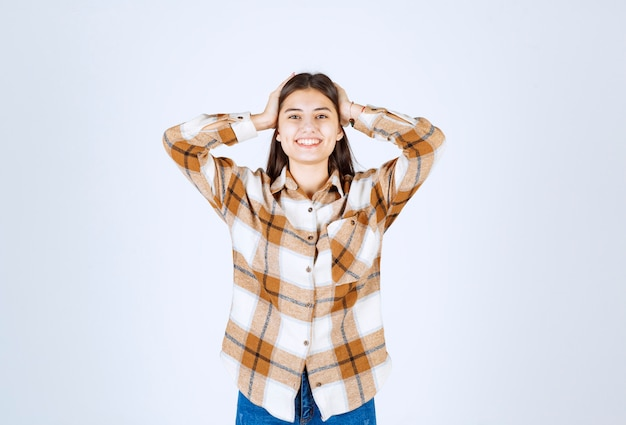 Positive young girl standing and posing on white-gray wall.