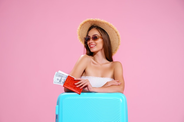 Positive young girl in straw hat and sunglasses with tickets and suitcase pink studio background smi...