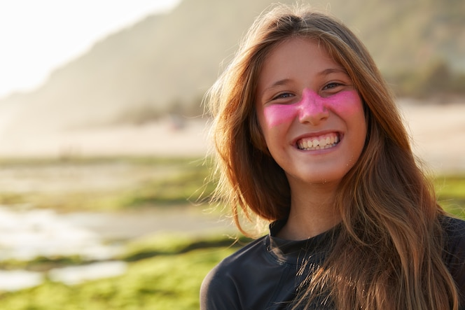 Positive young glad european woman with toothy smile, has protective zinc mask on face which blocks sun rays, wears diving suit for surfing, poses outdoor against blurred coastline wall.