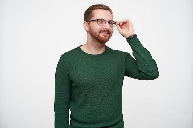 Positivo giovane bel ragazzo barbuto che tiene i suoi occhiali con la mano alzata e sorride sinceramente mentre guarda davanti a sé, in piedi