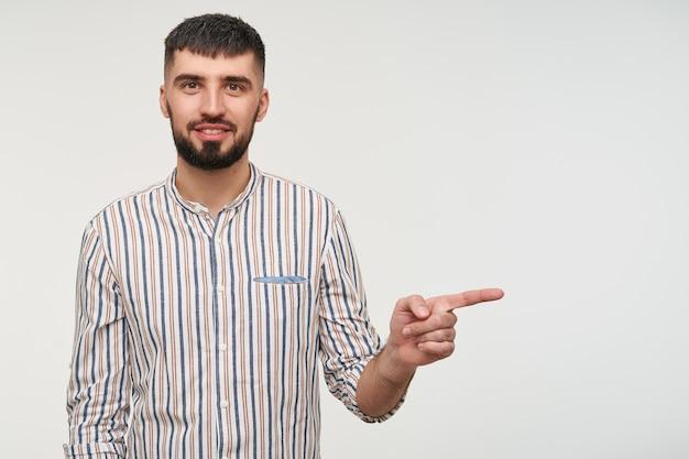 Позитивный молодой красивый бородатый мужчина брюнетки слегка улыбается и показывает в сторону с поднятым указательным пальцем, одетый в повседневную одежду, позируя над белой стеной
