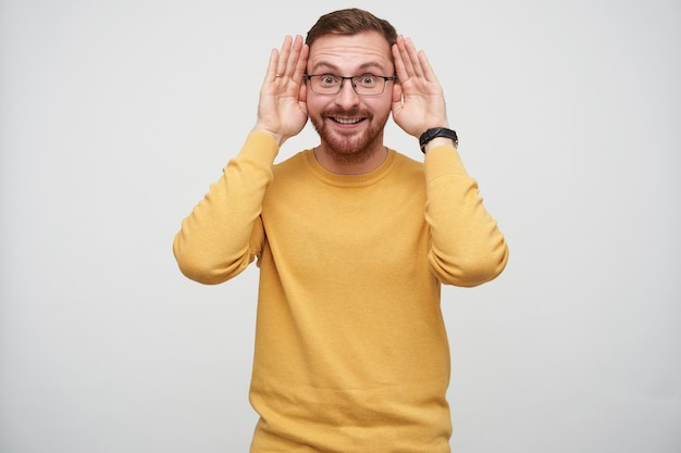 Positivo giovane maschio brunetta bello con la barba con gli occhiali e maglione senape mentre posa, sollevando le sopracciglia mentre guarda e mantenendo i palmi sulle tempie
