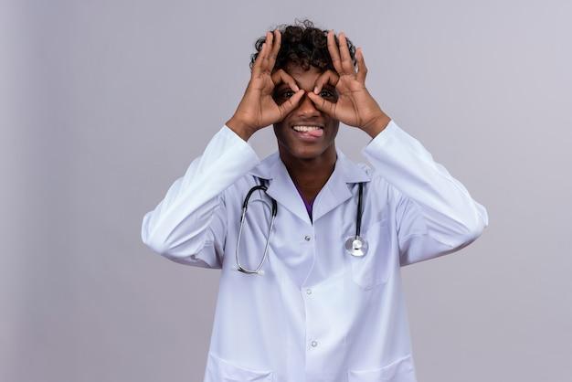 Un giovane medico dalla carnagione scura bello positivo con capelli ricci che porta il camice bianco con lo stetoscopio che guarda attraverso i fori dalle dita