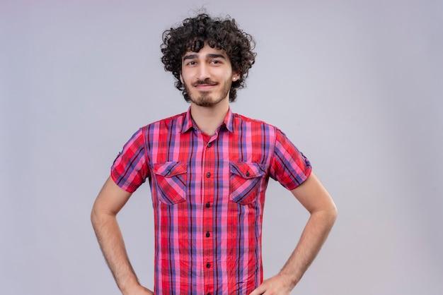 Un giovane uomo bello positivo con capelli ricci in camicia controllata che tiene le mani sulla vita