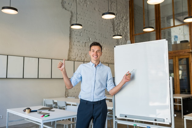 Positive young handsome smiling man standing at empty white board with marker,