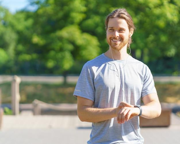 Позитивный молодой красивый спортсмен в наушниках с помощью фитнес-браслета во время тренировки на открытом воздухе
