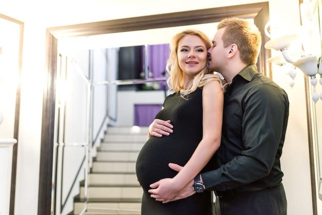 그의 새 아파트에서 신생아를 기대하는 동안 긍정적 인 젊은 행복 부부 매력적인 아내와 돌보는 남편이 임신 배꼽을 만지고