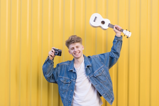 Positive young hipsters with ukulele and camera in their hands poses against the yellow wall