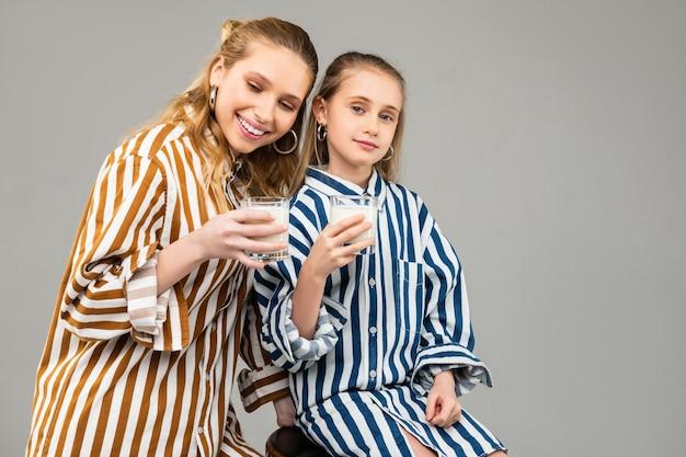 Позитивные молодые дамы проводят время вместе и пьют молоко из наполненных стаканов