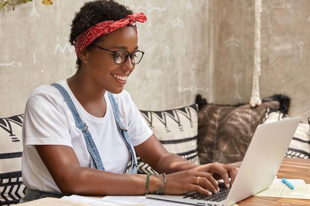 노트북 컴퓨터에 안경 키보드 정보에 긍정적 인 젊은 아가씨 프리랜서