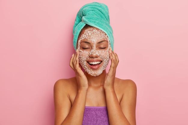 긍정적 인 젊은 여성은 특별한 스크럽으로 얼굴을 마사지하고, 뺨의 어두운 점을 줄이고, 미용 치료의 즐거움을 느끼고, 피부 문제가 있으며, 머리카락을 걱정하고, 수건으로 싸여 있습니다. 높은 해상도