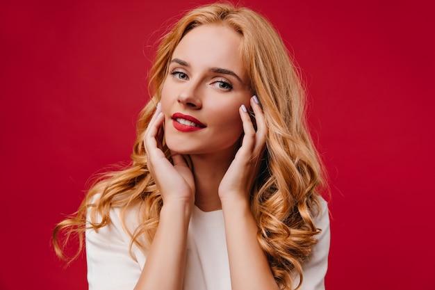 魅力的な笑顔でポーズをとるポジティブな若い女性。赤い壁に隔離された明るいブロンドの女の子。