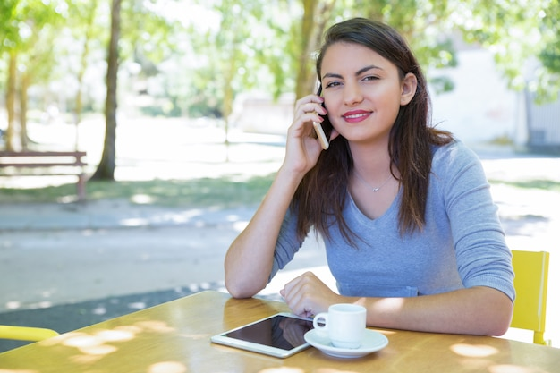 Positive young lady talking on phone at cafe table in park