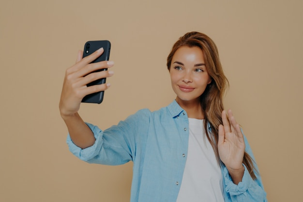 Positive young lady waving at camera on mobile phone while taking photo of herself or talking via video chat, recording video for social media on modern smartphone, posing on beige background