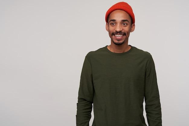 赤い帽子とカジュアルな服を着たポジティブな若い素敵なひげを生やした暗い肌のブルネットの男性は、手を下に向けて白の上に立っている間、魅力的な笑顔で脇を見ています