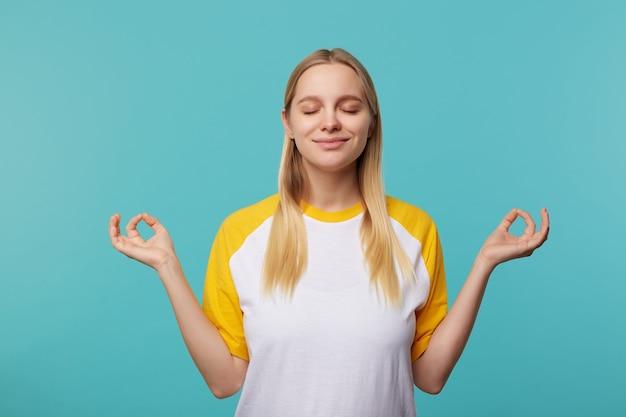 Позитивная молодая милая блондинка с повседневной прической, приятно улыбаясь с закрытыми глазами во время медитации, складывая пальцы в жесте мудры, позируя на синем фоне