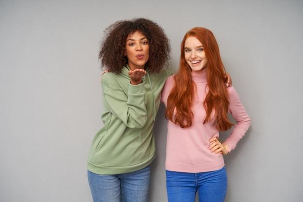 若いかなり陽気な赤毛の女性と灰色の壁を越えてポーズをとっている間、空気のキスを送信するポジティブな若い素敵な茶色の髪の巻き毛の暗い肌の女性