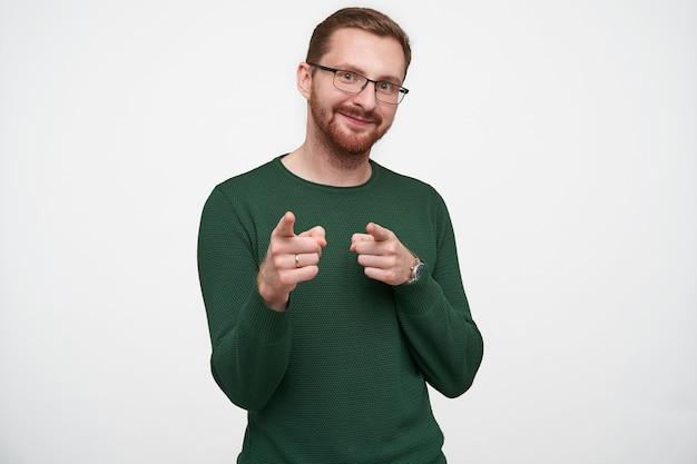 Позитивный молодой симпатичный брюнет с бородой с короткой стрижкой, указывающий с поднятыми указательными пальцами и приятно улыбающийся, в зеленом свитере и очках