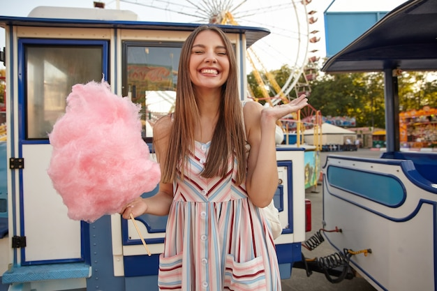 긴 머리를 가진 긍정적 인 젊은 사랑스러운 갈색 머리 여자, 놀이 공원 위에 포즈를 취하고, 손에 분홍색 솜사탕을 들고 눈을 감고, 손바닥을 올리고 유쾌하게 웃고