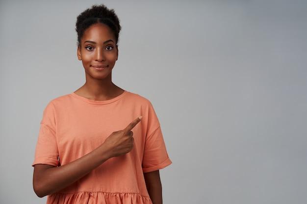 Positiva giovane bella donna bruna riccia con la pelle scura che mostra da parte con il dito indice e sorride leggermente, in piedi sul grigio