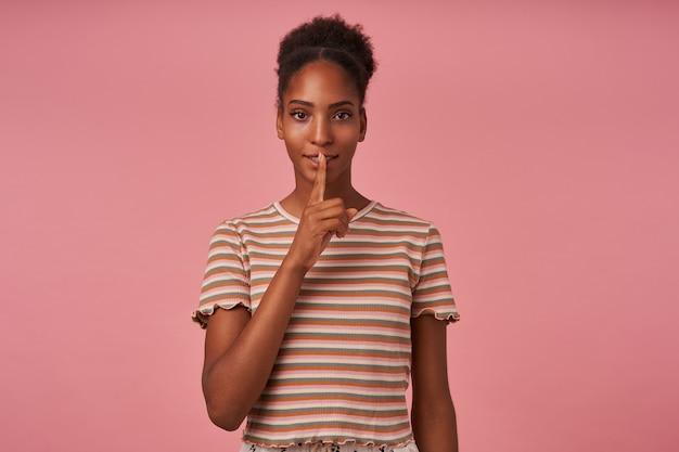 ピンクの壁の上に立って、彼女の秘密を守るように頼んでいる間、彼女の口に人差し指を持っているパンの髪型を持つポジティブな若い素敵な巻き毛のブルネットの女性 無料写真