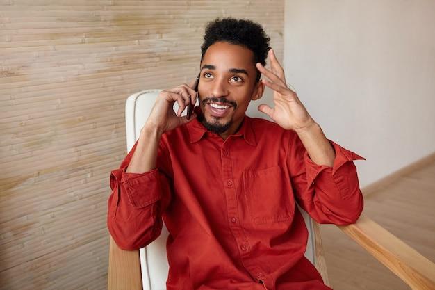 Positivo giovane maschio barbuto dai capelli scuri adorabile vestito con una camicia rossa che appoggia la testa sulla mano sollevata pur avendo una piacevole conversazione telefonica, isolato sull'interno della casa