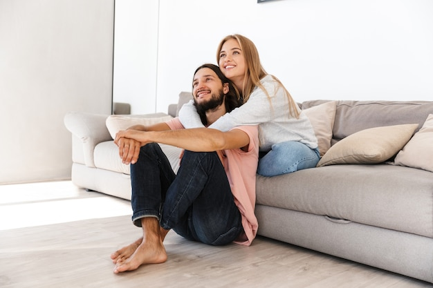 A positive young loving couple on sofa watch tv film indoors at home looking aside.