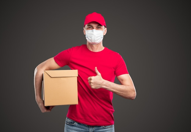 Positive young male courier in red cap and t shirt with protective mask on face holding craft box and showing thumb up gesture, while standing against gray background