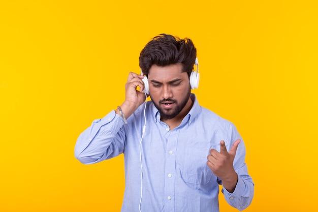긍정적 인 젊은 남성은 스마트 폰 헤드폰을 사용하여 좋아하는 온라인 라디오를 듣고