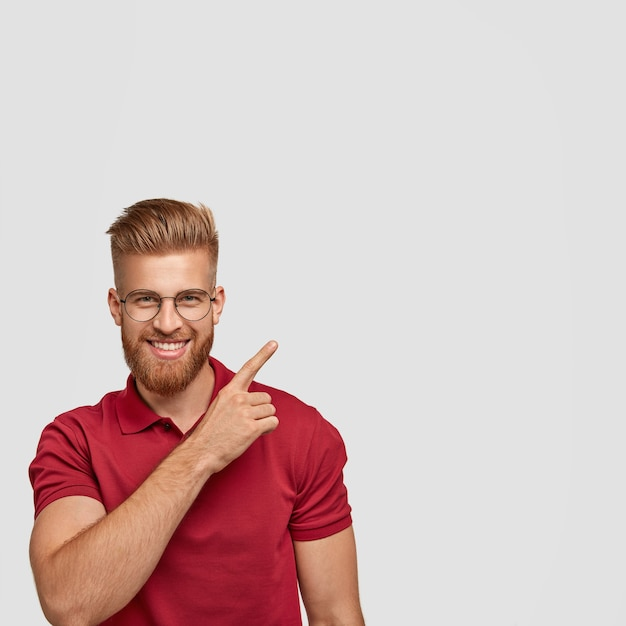 Positive young man being satisfied with results of work, has friendly pleasant smile, points upwards with fore finger, wears casual clothes, stands in against white wall