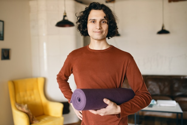 Giovane positivo in abiti casual che tiene il rotolo di stuoia di yoga sotto il braccio andando a praticare in casa, felice di rimanere a casa durante la quarantena, dedicando più tempo allo sviluppo personale e ad attività salutari