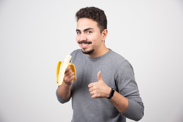 Positive young man holding banana and showing a thumb up.