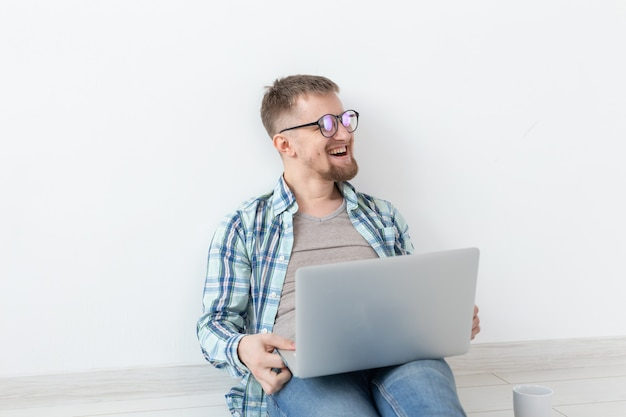 Позитивный молодой человек в повседневной одежде и очках просматривает интернет с помощью wi-fi и ноутбука в поисках съемного жилья. концепция новоселья и поиска квартиры. Premium Фотографии