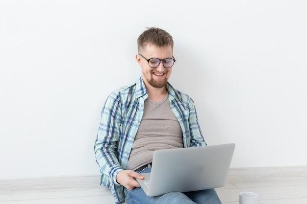 Позитивный молодой человек в повседневной одежде бродит по интернету в поисках нового жилья, сидя на полу в пустой комнате. концепция поиска квартиры с помощью интернета и ноутбука. copyspace