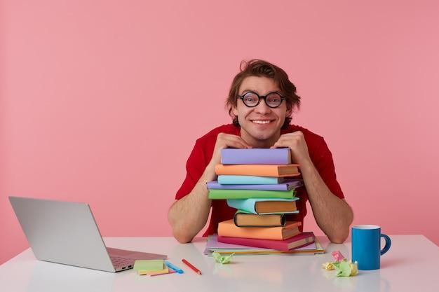 眼鏡をかけたポジティブな若い男は赤いtシャツを着て、男はテーブルのそばに座って、ピンクの背景の上に隔離された本の山に寄りかかって、ラップトップと本で作業しています。幸せで嬉しそうに見えます。