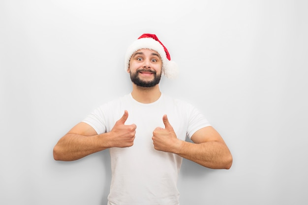 Positive young man looks  . he shows his big thumbs up. guy wears chritmas hat.