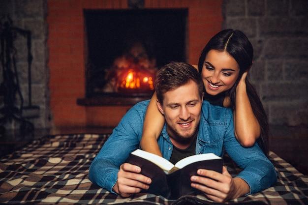 床に横たわって読んでいる肯定的な若い男と開いた本。美しいモデルが彼の後ろにいます。彼女は本を見下ろして微笑んでいます。彼らは暖炉の近くで一緒に時間を過ごします。