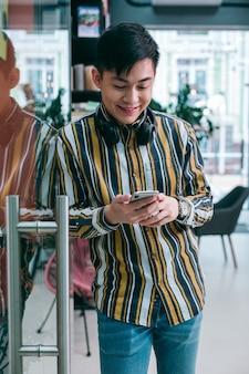 Позитивный молодой человек рядом со стеклянной дверью в офисе, глядя на экран смартфона с улыбкой