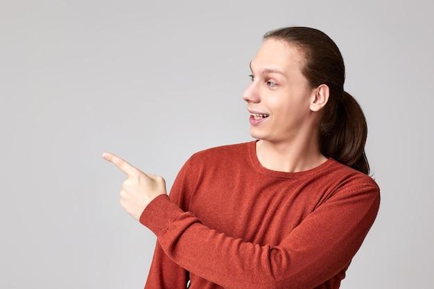 Позитивный молодой человек, указывая пальцем на пустое место для рекламы