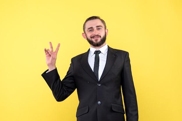 Положительный молодой человек показывает знак победы