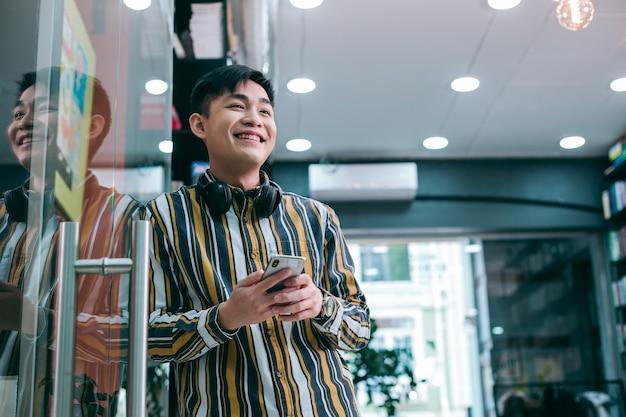 Позитивный молодой человек, стоящий в офисе возле стеклянной двери и с улыбкой глядя в сторону. баннер веб-сайта