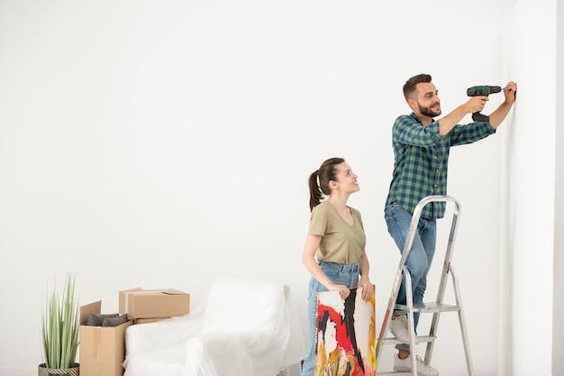 ステップのはしごの上に立って、写真のネジを挿入しながら電動ドライバーを使用してポジティブな若い男