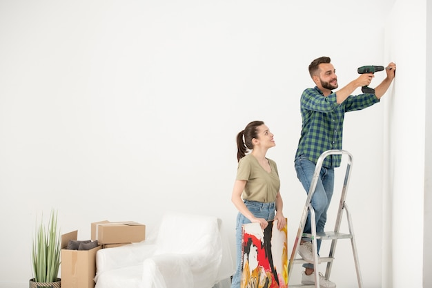 Positive young man standing on step ladder and using electric screwdriver while inserting screw for picture