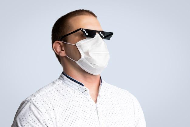 肯定的な若い男がピクセルサングラスと衛生マスクを身に着けて感染、インフルエンザなどの空中呼吸器疾患、分離された青の2019-ncovを防ぐ