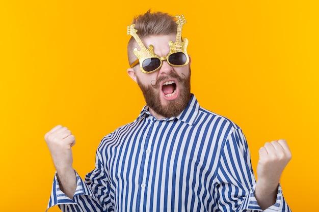 ギターの形で眼鏡をかけた前向きな青年が黄色い壁に喜ぶ