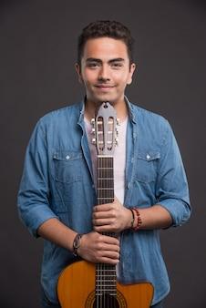 Положительный молодой человек с гитарой, стоя на темном фоне.